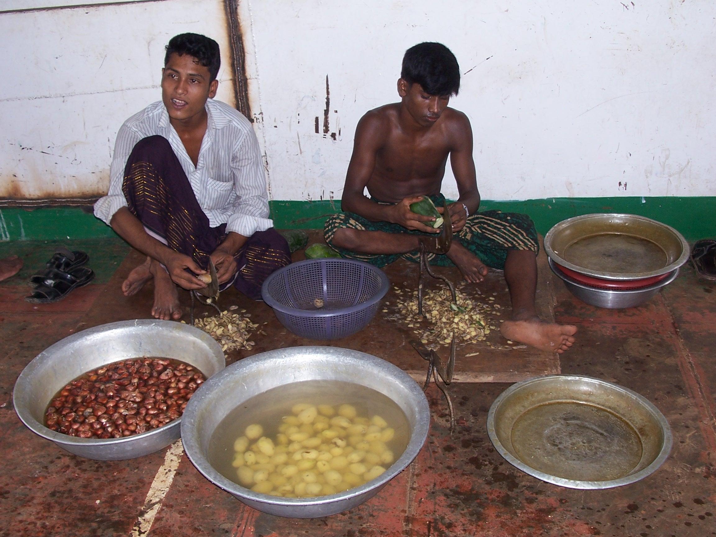 Two men cooking vegetables
