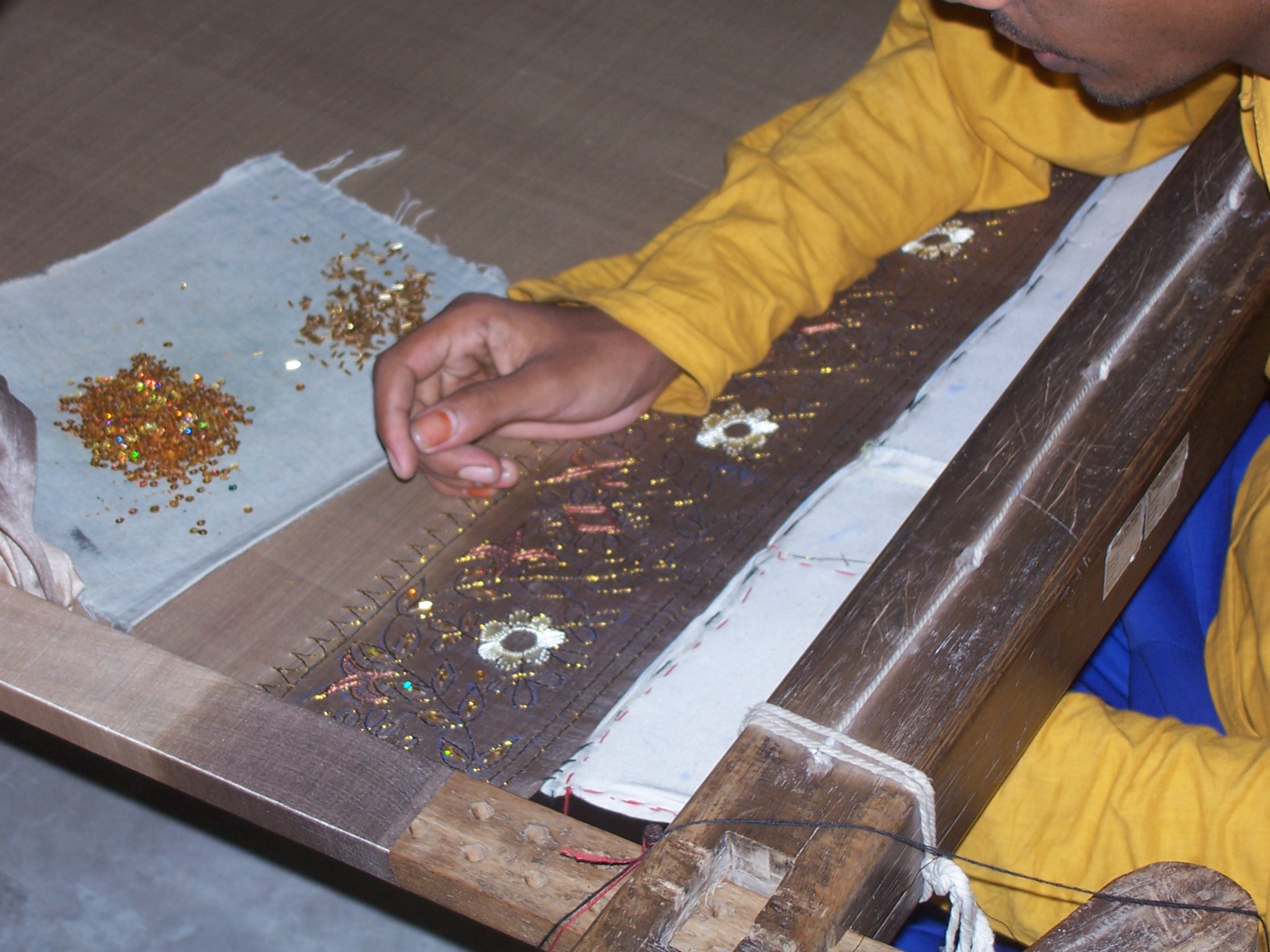 A silk product being beaded by hand