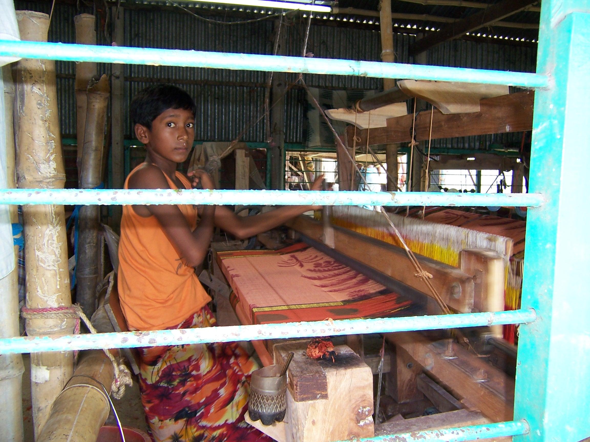 A boy working on silk in a factory