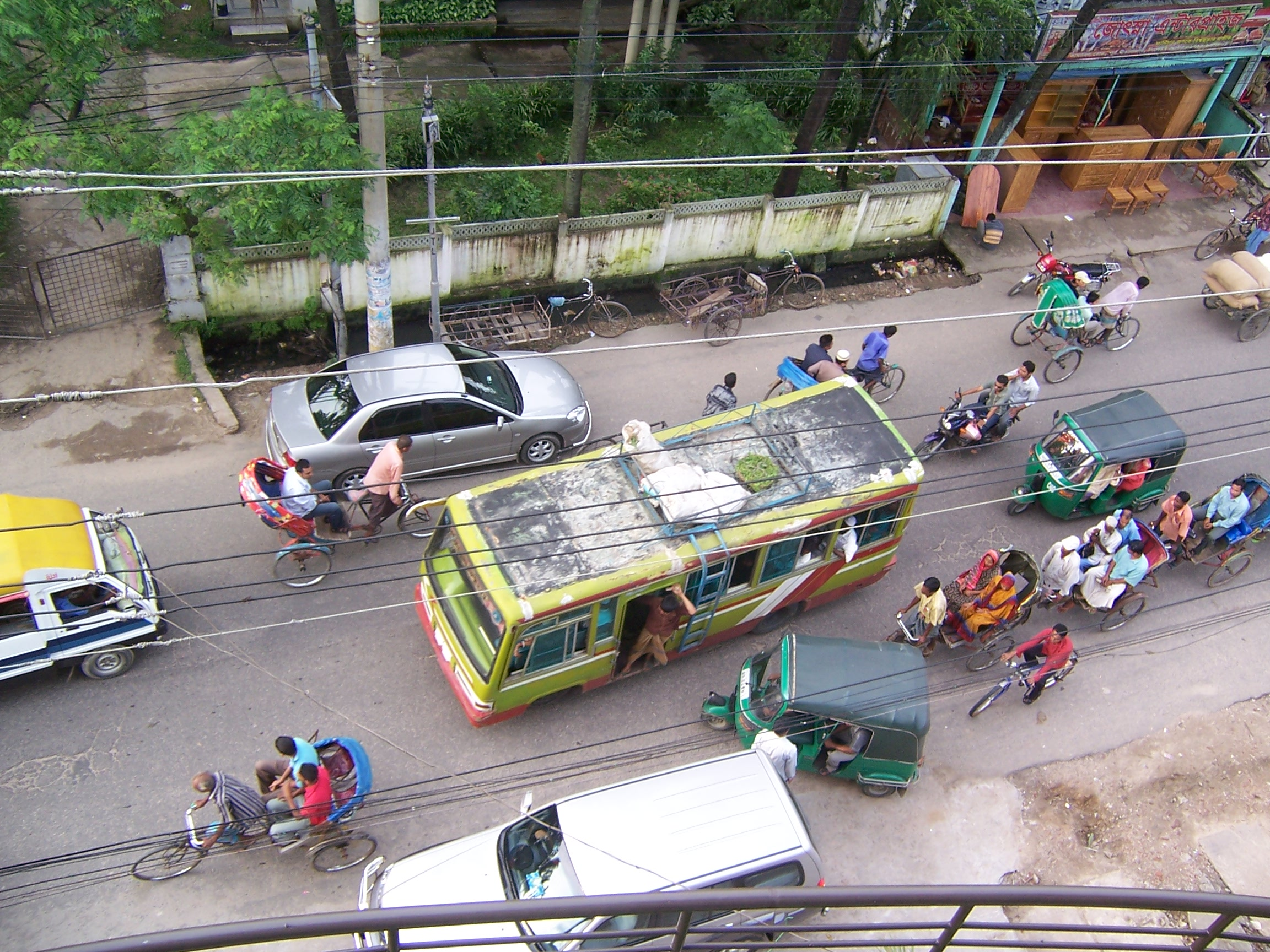 Bikes, carts, cars, and busses fill the busy street