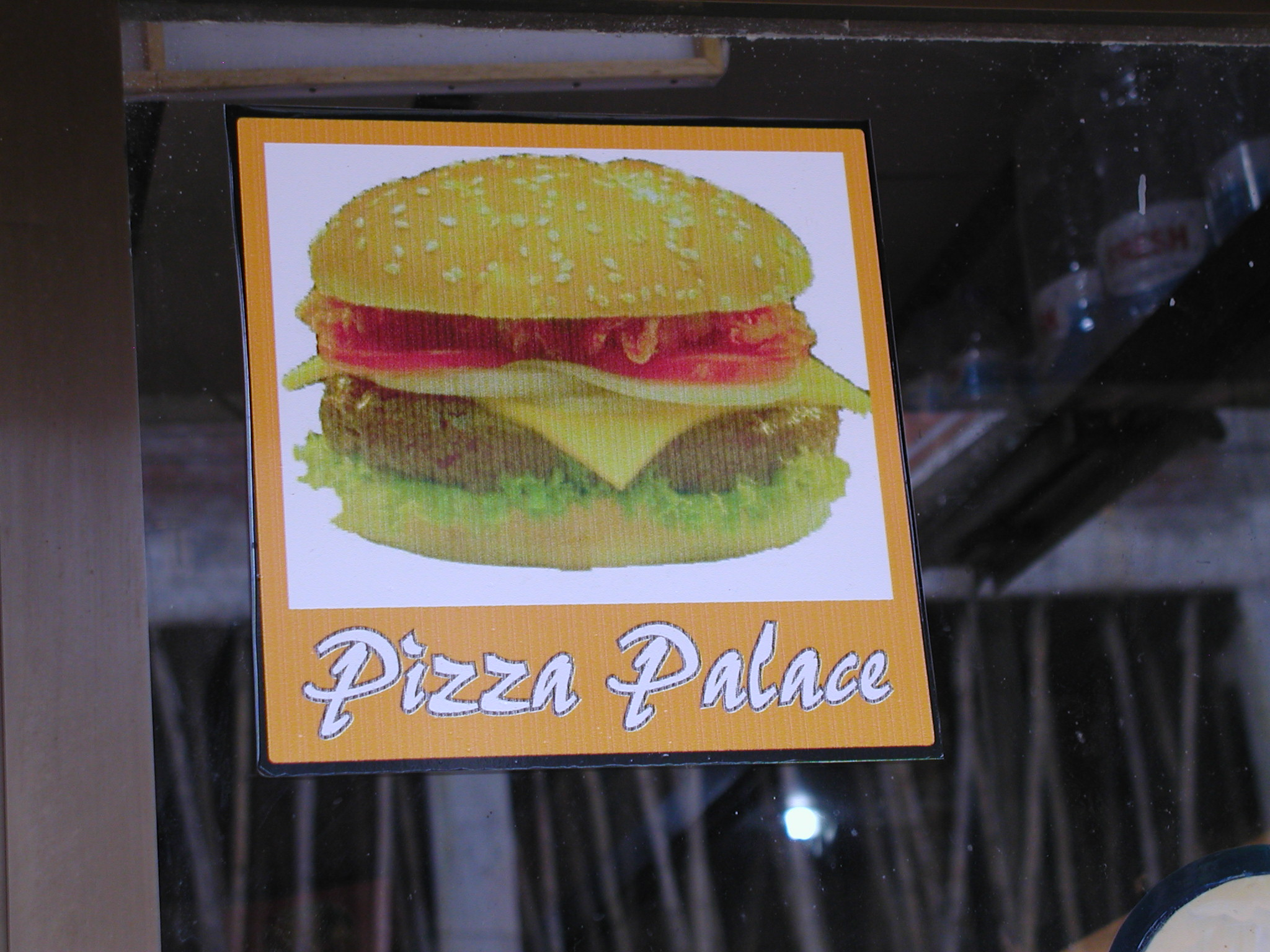 A sign for the restaurant pizza palace with a photo of a cheeseburger